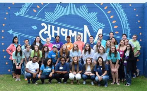student leaders in front of a Memphis mural